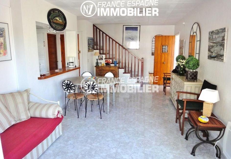 roses immobilier: villa 133 m², salon / séjour avec cuisine semi ouverte, étage escalier