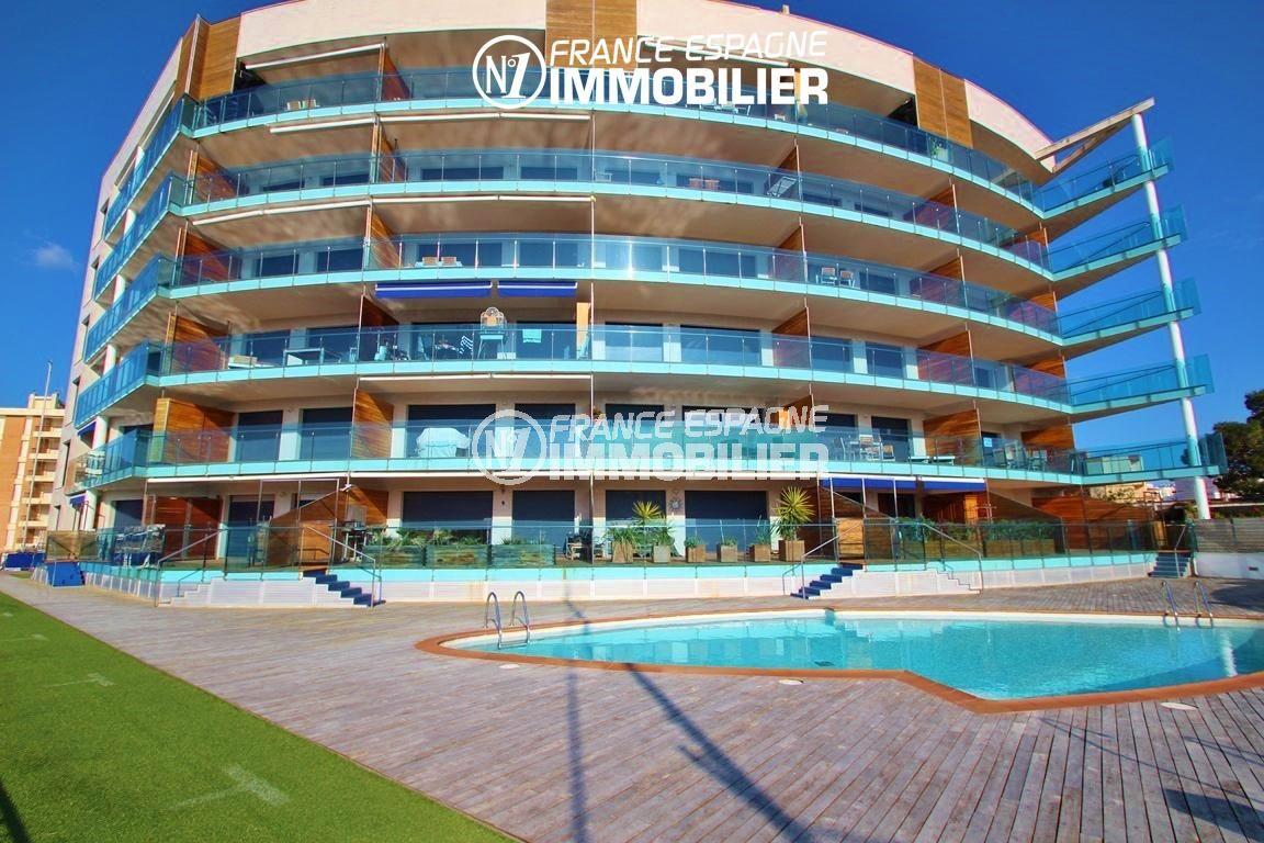 appartement costa brava, ref.2848, façade bleutée de l'immeuble avec sa piscine et ses abords en bois