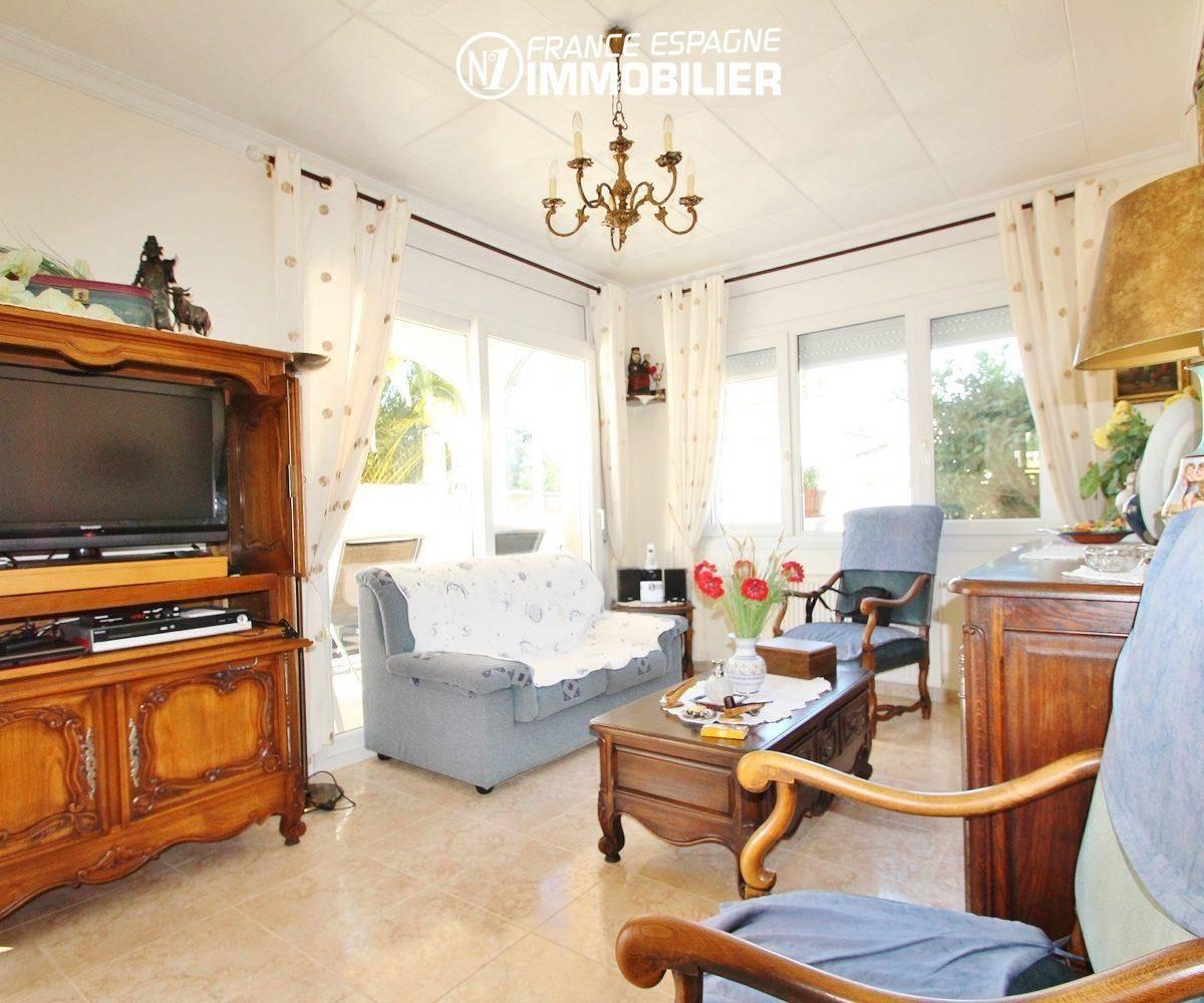 maison a vendre costa brava, vue sur le séjour avec accès terrasse, jardin & piscine