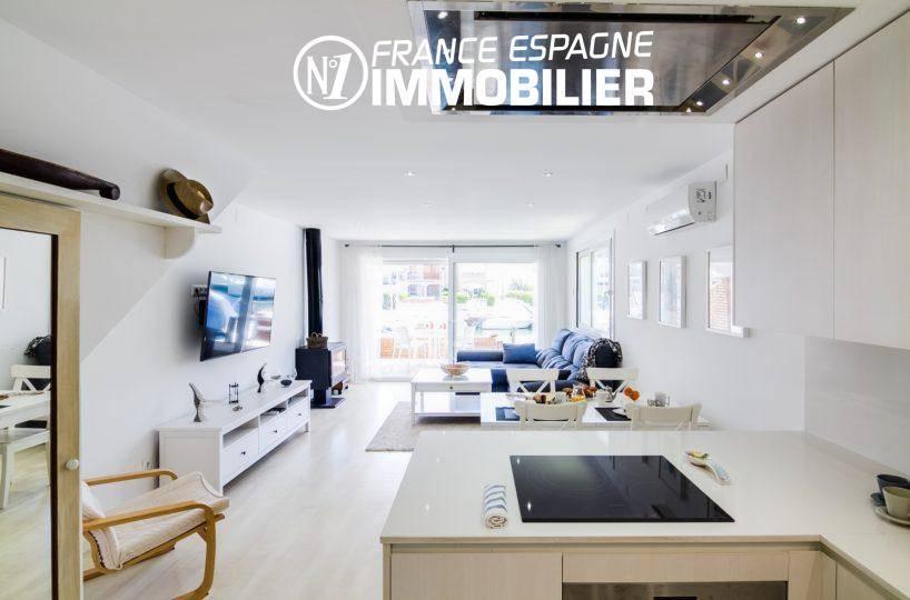 agence immo empuriabrava: villa ref.3305, aperçu depuis la cuisine, table de cuisson et séjour en arrière plan