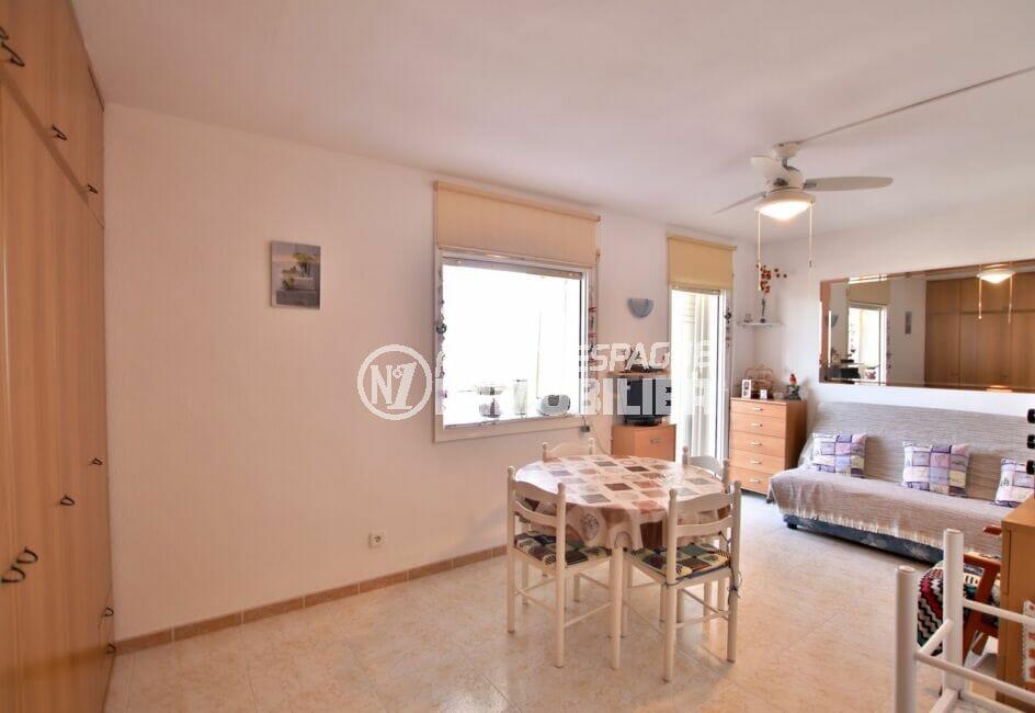 residence santa margarita rosas: studio 37 m² vue canal, salon avec table, chaises, canapé et grande armoire