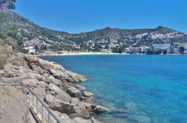 petit chemin autour des rochers menant à cette jolie plage ensoleillée