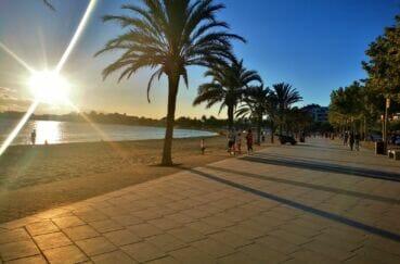 coucher de soleil sur la baie de roses et la longue promenade du bord de mer