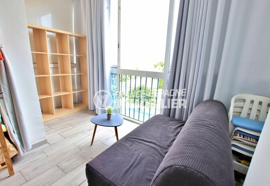 vente appartement rosas, 27 m² avec son coin salon aménagé d'un canapé et étagères, table basse