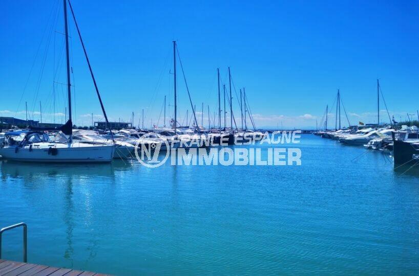 le port de plaisance de roses avec ses jet-ski, bateaux à moteurs, voiliers, et catamaans