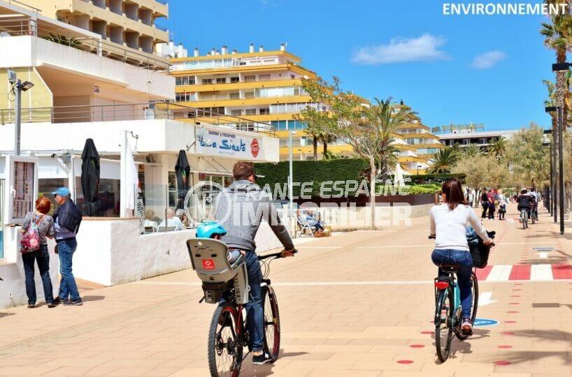 promenade en vélo le long de la plage de rosas avec ses boutiques et restaurants